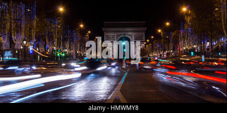 Champs Elysees in Paris illuminated for Christmas and Triumphal Arch in background - Stock Photo
