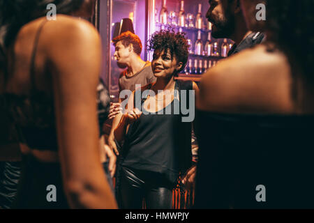 Beautiful young woman with her friends at nightclub. Young african female with friends at pub. - Stock Photo