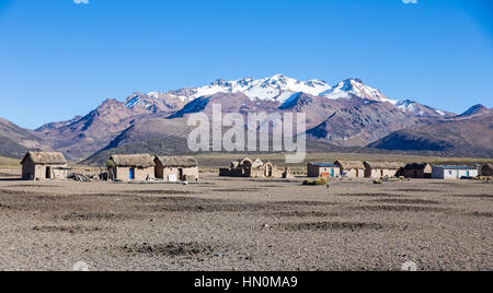 Small village of shepherds of llamas in the Andean mountains. High Andean tundra landscape in the mountains of the - Stock Photo
