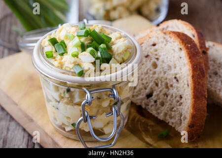 Egg dip sandwich with spring green onion for healthy and delicious brunch on rustic wooden chopping board - Stock Photo