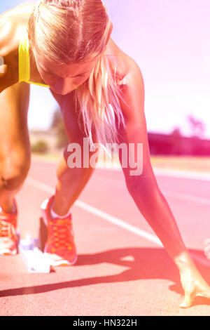 Female athlete ready to run on running track on a sunny day - Stock Photo