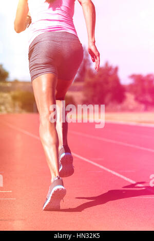 Rear view of female athlete running on running track on sunny day - Stock Photo