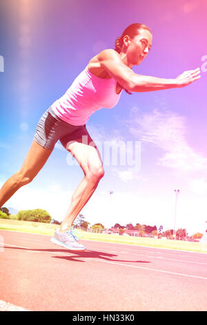Female athlete running on running track on sunny day - Stock Photo