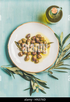 Pickled green Mediterranean olives on white ceramic plate, olive tree branch and virgin olive oil in glass bottle - Stock Photo