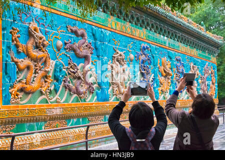 Tourists photographing Nine Dragon Wall in Beihai Park, Beijing, China - Stock Photo