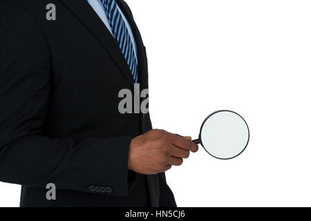 Mid section of businessman holding magnifying glass on white background - Stock Photo