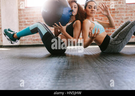 Two sporty women training with medicine ball in gym. Girls working out to shape their body. - Stock Photo