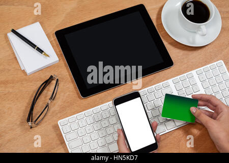 Close-up of businessman doing online shopping on mobile phone - Stock Photo