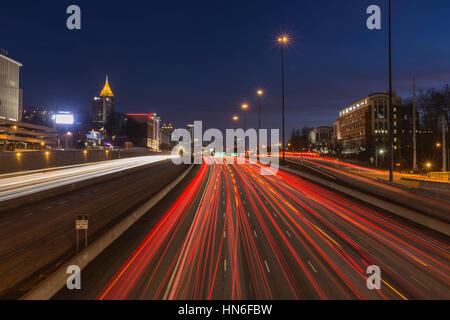 Atlanta, Georgia, USA - February 15, 2014:  Night freeway traffic in midtown Atlanta speeding towards downtown towers. - Stock Photo