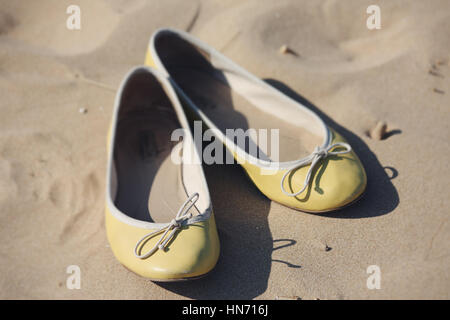 Yellow ballerina shoes lying on a sandy beach, while their owner bathed in the Mediterranean sea. - Stock Photo