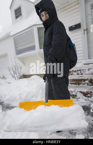 Merrick, New York, USA. 9th Feb, 2017. Teen boy, a 14-year-old from Merrick, volunteers to shovel show to help his - Stock Photo