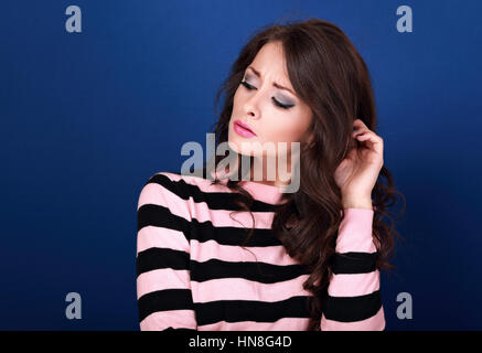 Thinking unhappy angry makeup with long curly hair style woman looking down and scratching the head blue empty copy - Stock Photo