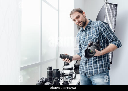 Photographer in his studio, he is holding a digital camera and choosing the right lens for his photo shoot - Stock Photo