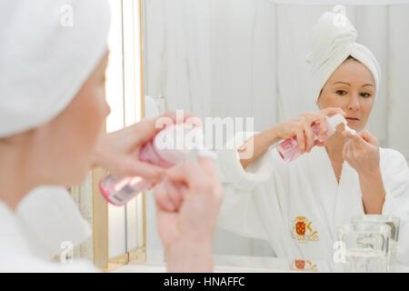 Junge Frau im Badezimmer verwendet Gesichtspflege - woman does face care - Stock Photo
