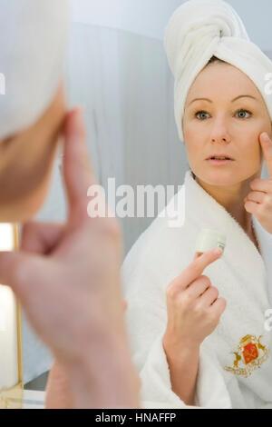 Junge Frau im Badezimmer verwendet Gesichtscreme - woman does face care - Stock Photo
