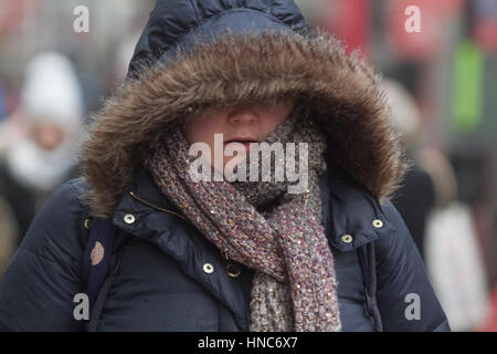 Wimbledon London, UK. 11th Feb, 2017. Pedestrians and shoppers in Wimbledon town centre brave the sleet and freezing - Stock Photo