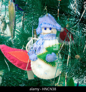 New Year background with Christmas toy snowman on the tree. - Stock Photo