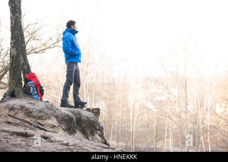 Side view of hiker standing on edge of cliff in forest - Stock Photo