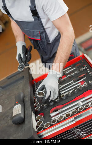High angle view of male mechanic arranging tools in drawer at car repair shop - Stock Photo