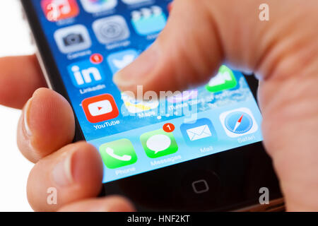 BATH, UK - JANUARY 15, 2014: Close-up of  an Apple iPhone 4s  screen with a man's thumb hovering above the text - Stock Photo