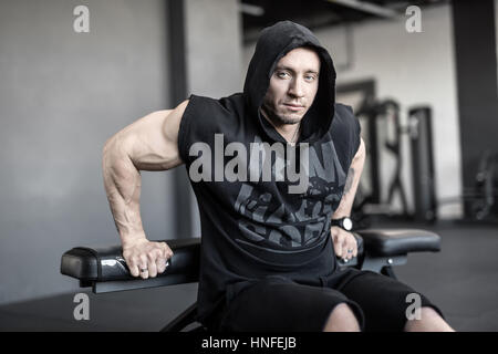 Brutal man with heavy muscles does lifting on the bench in the gym. He wears black hooded sleeveless and black shorts. - Stock Photo
