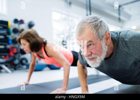 Senior couple in gym working out, doing push ups - Stock Photo
