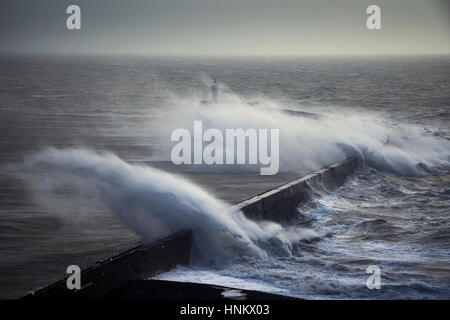 Huge waves crash over a sea wall near a lighthouse during a storm - Stock Photo