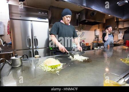 Okonomiyaki being prepared in a restaurant in Hiroshima, Japan - Stock Photo