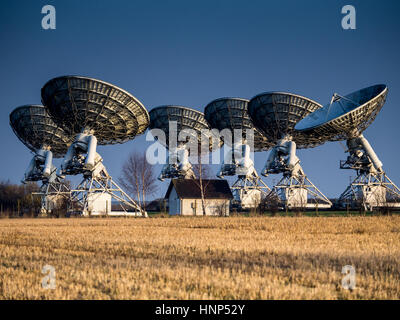 Several radio telescopes, part of the Mullard Radio Astronomy Observatory Arcminute Microkelvin Imager Large Array - Stock Photo