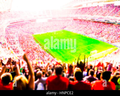 Football- soccer fans cheer their team and celebrate goal in full stadium with open air  with bright lighting beam - Stock Photo
