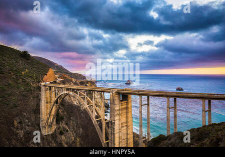 Scenic panoramic view of historic Bixby Creek Bridge along world famous Highway 1 in evening twilight with dramatic - Stock Photo