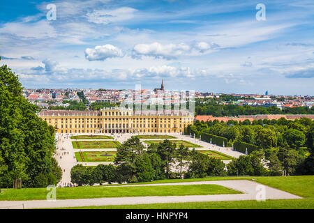 Classic view of famous Schonbrunn Palace with Great Parterre garden on a beautiful sunny day with blue sky and clouds - Stock Photo