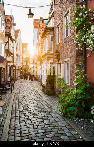 Vertical view of an old town in Europe in beautiful golden evening light at sunset in summer with pastel toned retro - Stock Photo