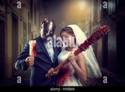 Maniac couple with bloody bat and meat cleaver in night city. Groom in hockey mask - Stock Photo