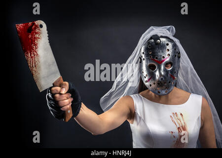 Bride maniac in hockey mask with bloody knife on black background - Stock Photo