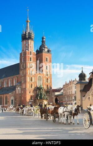 Carriage waiting for tourists, St Mary's Church in the background, Crackow, Poland, UNESCO - Stock Photo