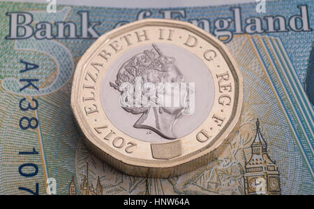 New pound coin with banknote background - Stock Photo