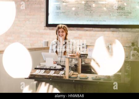 Cashier behind cash register in cafe - Stock Photo