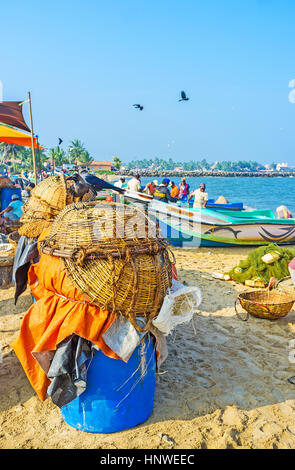 NEGOMBO, SRI LANKA - NOVEMBER 25, 2016: The drying inverted baskets at the sandy beach of fishing port with the - Stock Photo