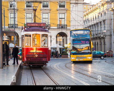 LISBON, PORTUGAL - JANUARY 10, 2017: Transport in Lisbon: typical old tram and a touristic bus on the Praca do Comercio - Stock Photo