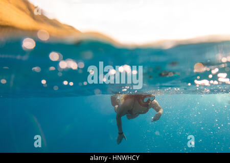 Woman swimming underwater, Oahu, Hawaii, USA - Stock Photo