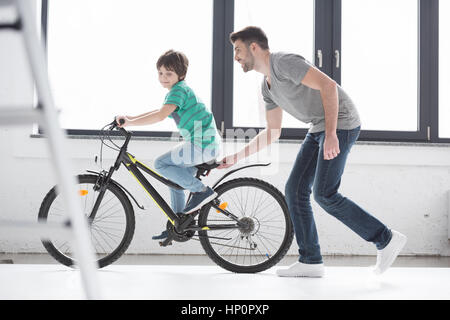 young father helping son to ride bicycle - Stock Photo