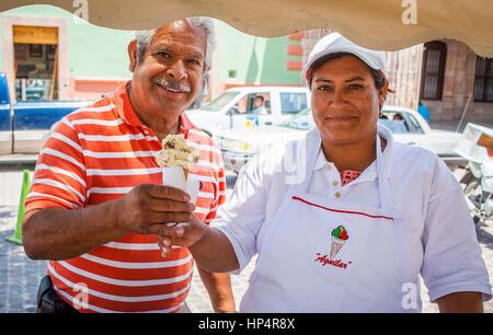 ice cream stand (nieves),customer and salesperson, Plaza Principal, Dolores Hidalgo, Guanajuato State, Mexico - Stock Photo