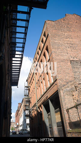 Metal fire escape ladder and former office building and warehouse in former commercial district, Manchester, UK - Stock Photo