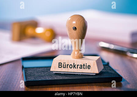 A stamp with the inscription bureaucracy stands on a desk. - Stock Photo