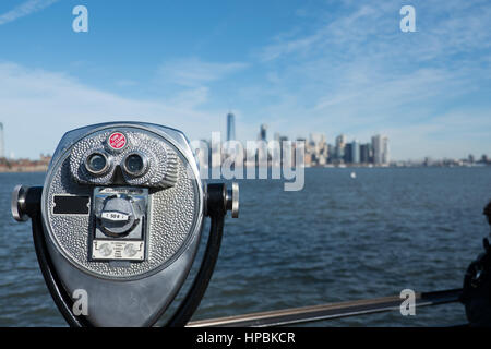Tower viewer binoculars in foreground blurred New York City skyline in background overlooking Hudson River and the - Stock Photo