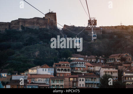 Tbilisi Old Town and Narikala Fortress on the background of the Cabs of the cableway at sunset. Landmark of Georgia - Stock Photo