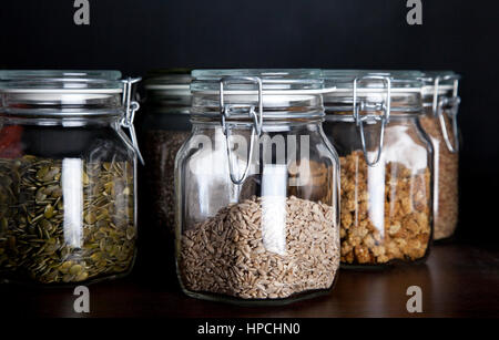 Pumpkin seed, sunflower seed and mulberries in glass jars with black background - Stock Photo