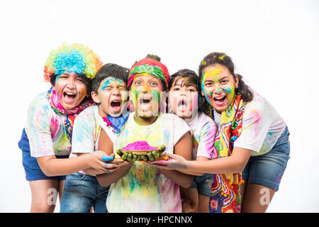 five or 5 cute little indian kids playing with colours or asian children celebrating holi over white background - Stock Photo