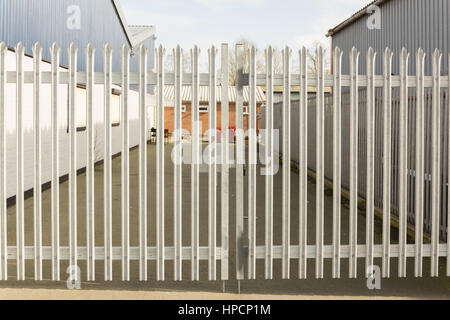 Set of locked spiked security gates at an industrial or commercial premises - Stock Photo